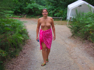 Tessa is wearing a pareo around her waist, but no top. It's not common to wear tops on a nudist resort or camp site
